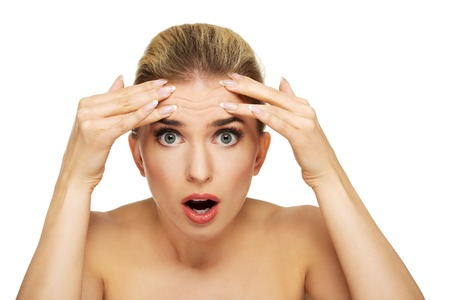 A young woman checking wrinkles on her forehead, closeup Stock Photo