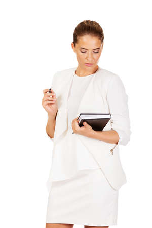Young businesswoman thinks about some idea and makes a notes.