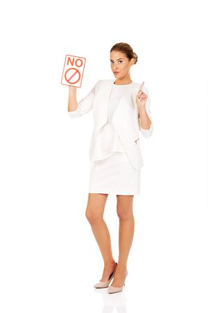 Young businesswoman holding a board with ban. Banque d'images