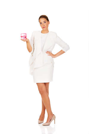 Young businesswoman holding pink rubber stamp.