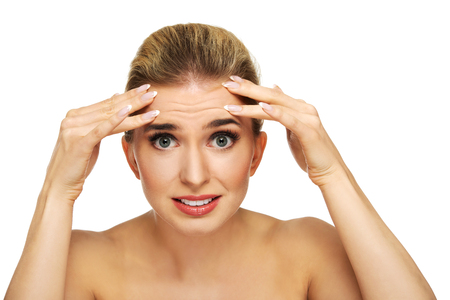 A young woman checking wrinkles on her forehead, closeup Stockfoto