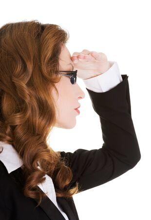 Zakenvrouw op zoek ergens ver weg met de hand boven de ogen.
