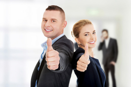 Happy business couple showing thumbs up.