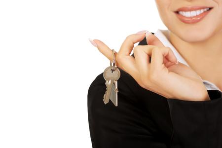 Glimlach zakenvrouw makelaar geven sleutels. Stockfoto