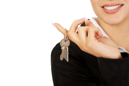 Smile businesswoman real estate agent giving keys.
