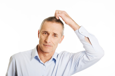 Mature confused man scratching his head. Stock Photo