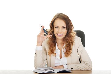 Happy zakenvrouw met note en pen op een bureau.
