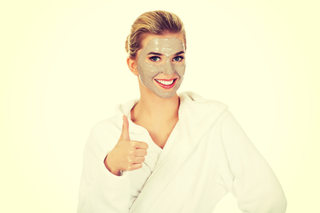Young woman with facial mask shows ok sign,isolated on white.