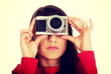 Mujer joven que toma una foto con la cámara.
