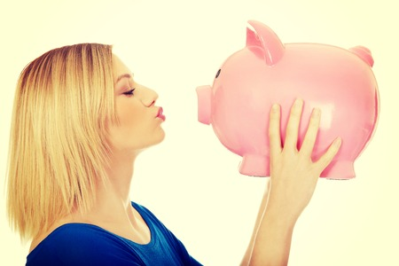 Happy casual woman kissing a piggybank.