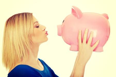 Casual mujer feliz que besa a una hucha.