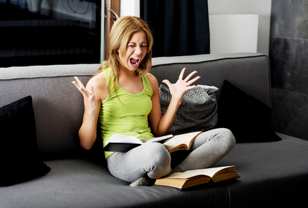 Young angry teenage woman learning to exam on a sofa.