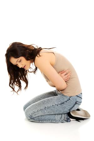 Junge Kursteilnehmerfrau zusammengerollt mit einem riesigen Magenschmerzen. Standard-Bild