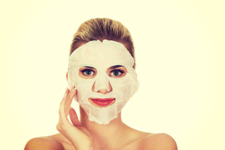Young happy woman with facial mask, isolated on white.