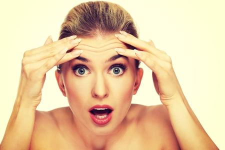 Una mujer joven, comprobación de las arrugas en la frente, de cerca