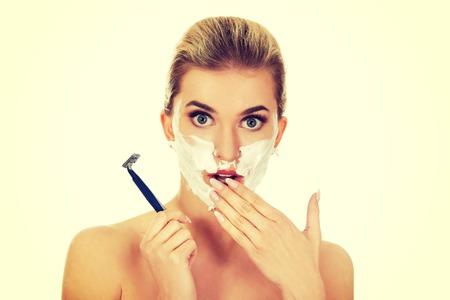 Jonge geschokte vrouw scheren van haar gezicht met een scheermes, geïsoleerd op wit Stockfoto