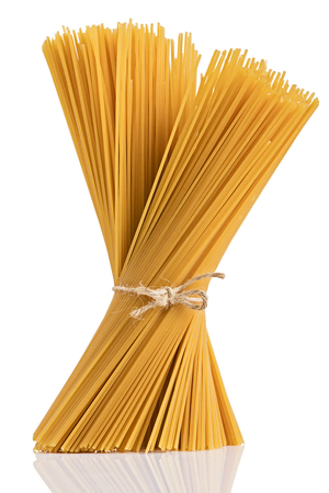 Uncooked dry fettuccine pasta isolated on a white background. Foto de archivo