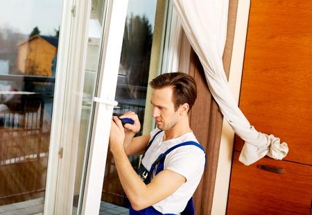 Jonge handyman reparatie venster met schroevendraaier. Stockfoto