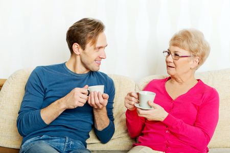 Mother and son sitting on couch and drinking tea or coffee.