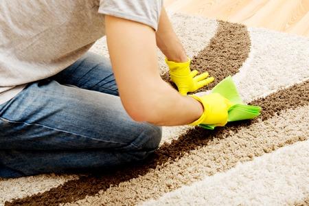 Mens in gele handschoenen reinigen van tapijt. Stockfoto