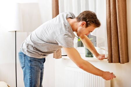 Young man changing temperature of radiator. Stockfoto