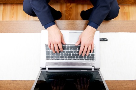 Aerial view of man's hands on laptop.