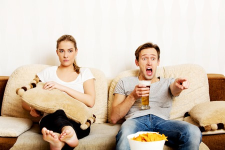 Woman sitting bored while man watching sports.