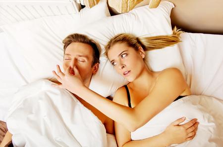 Paar in bed, kan de mens snurken vrouw niet slapen. Stockfoto