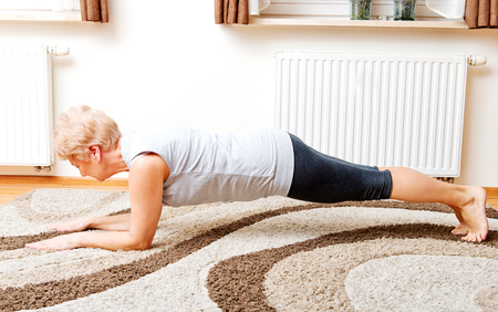 Senior woman doing yoga in living room.