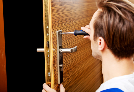 Young man fixing the door with screwdriver. Archivio Fotografico