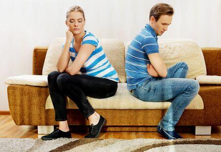 pareja ofendida sentados espalda con espalda en el sofá.