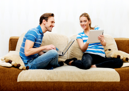 Young couple relaxing on sofa and using tablet and laptop.
