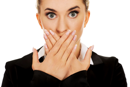 Young businesswoman covering with hand her mouth. Speak no evil concept. Stock Photo
