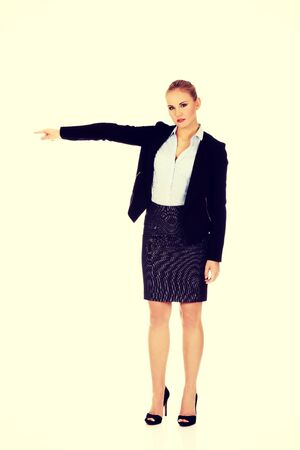 Angry business woman shows get out gesture. Banque d'images