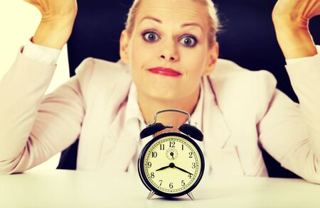 Surprised business woman lsitting behind the desk with alarm clock. Stock Photo