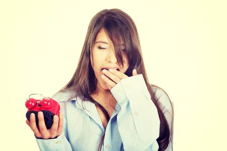 Young yawning woman in big shirt holding alarm clock.