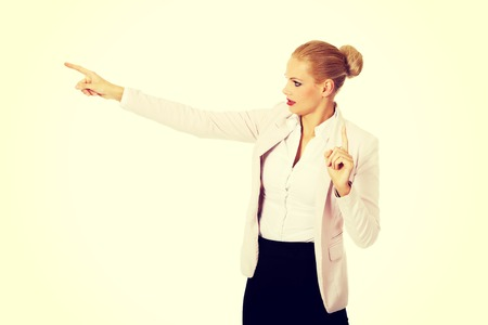 Young focus business woman explaining something and pointing at board or copyspace. Banque d'images