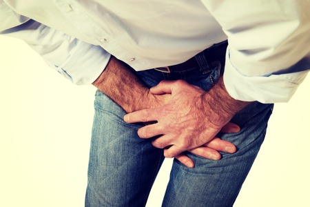 Mature man covering his painful crotch. Stock Photo