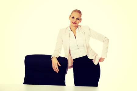 Young busiess woman standing behind the desk leanig on armchair.