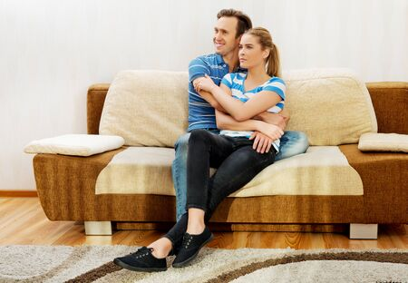Smiling loving couple sitting on couch. Stock Photo