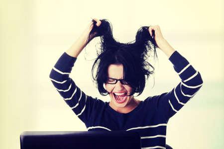 Mujer frustrada que trabaja en la computadora portátil, aislado en blanco