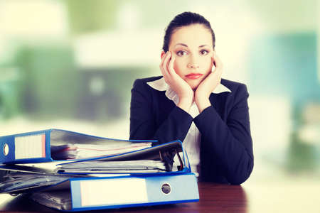 Sad woman with ringbinders sitting at the desk. Tired and exhousted business woman. Stock Photo
