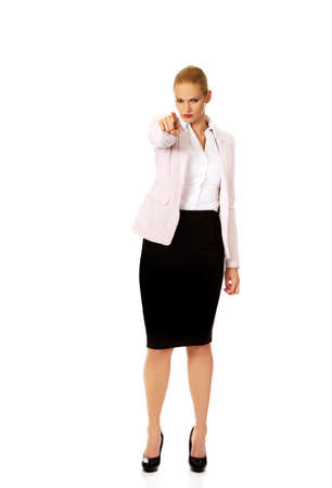 Angry business woman pointing at camera.