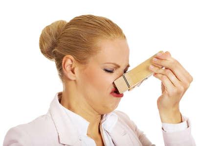 彼女の鼻に巨大な洗濯はさみと若いビジネス女性。コンセプトは悪臭を放ちます。