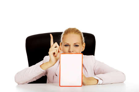 Young business woman sitting behind the desk and holding a board with ban.
