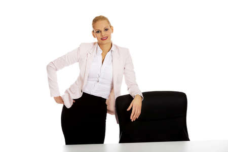 Young busiess woman standing behind the desk leanig on armchair Banque d'images