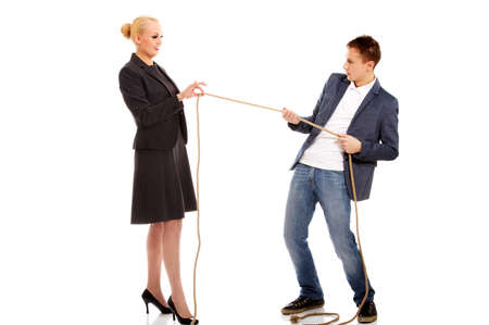 Boss concept-woman holding rope in two fingers, man pulling a rope and cant win Banque d'images