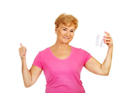 Smiling senior woman holding a tooth model and shows OK