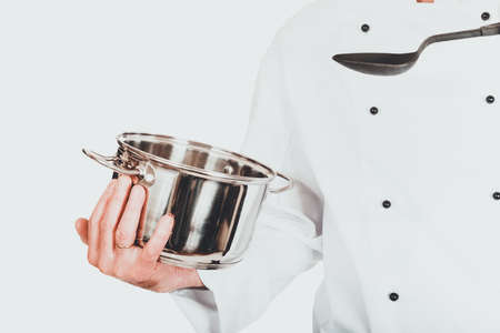 Chefs hand holding stainless steel pot and spoon Фото со стока