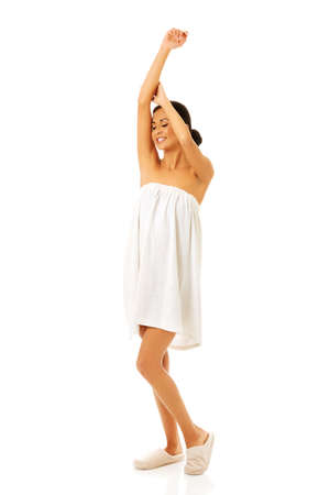 Woman wrapped in towel stretching arms